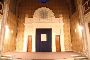 Installation. Der Vorhang zeigt im Akt der Verhüllung auf eine Leerstelle.